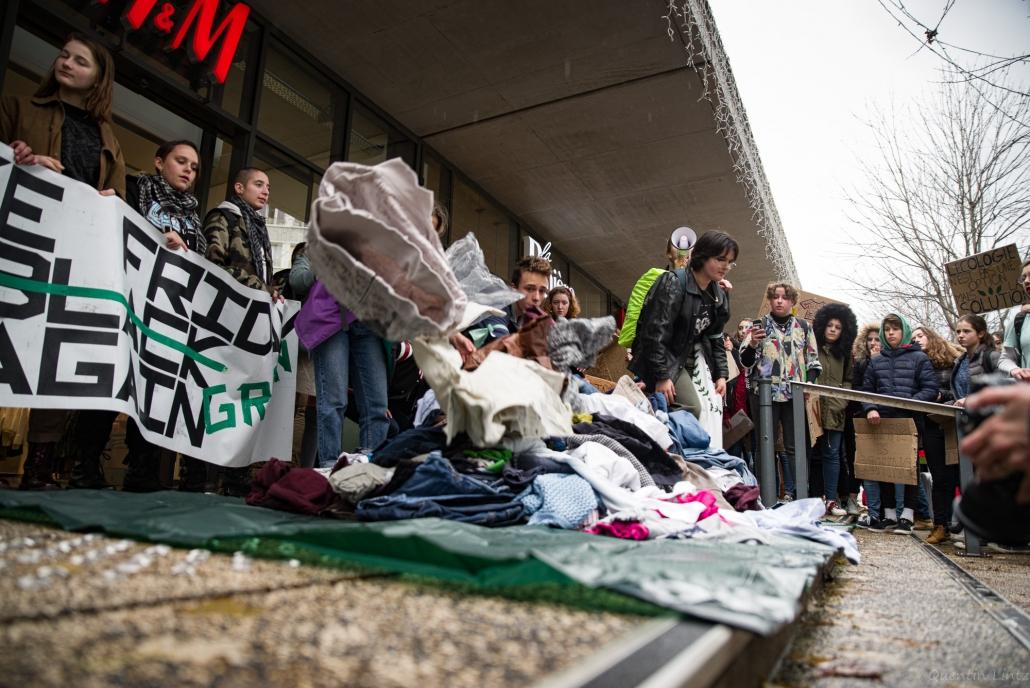 une montagne de vêtements est mise sous les yeux des manifestant.es