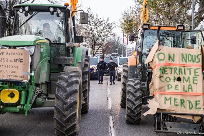 pancarte accroché au tracteurs et policiers derrière