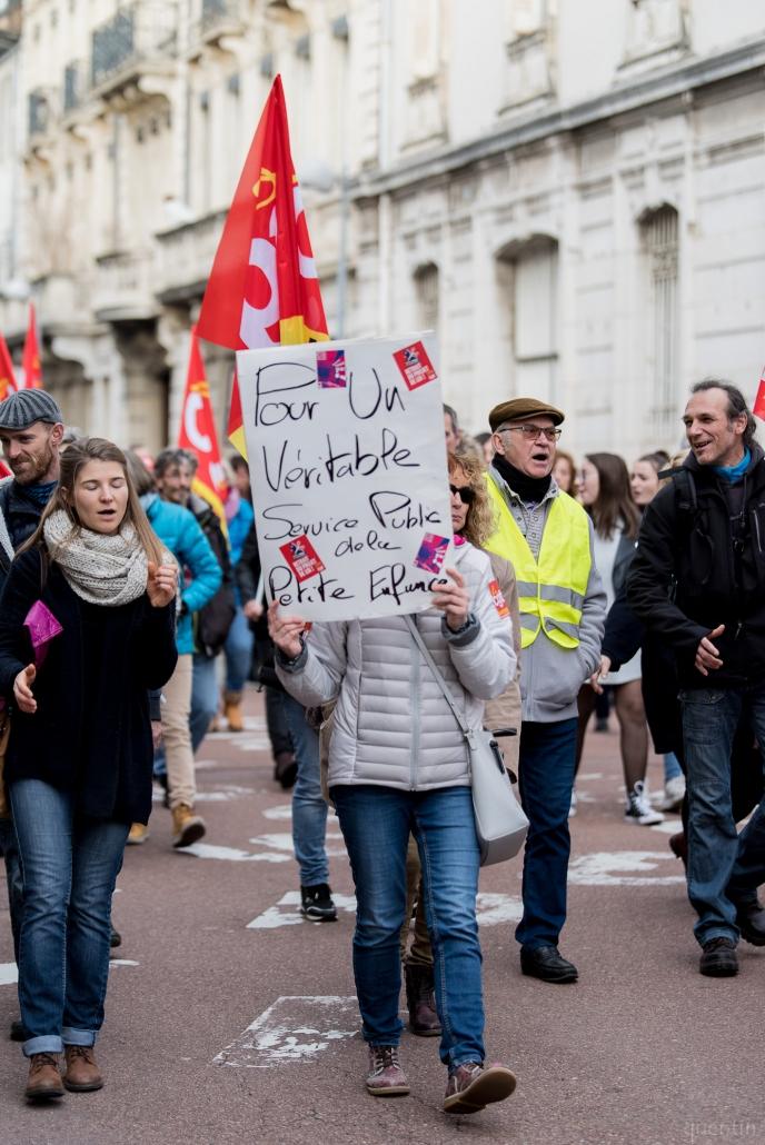 une manifestante se cache derrière sa pancarte