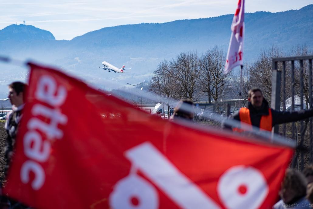 """avion décolant derrière le drapeaux """"attac"""""""