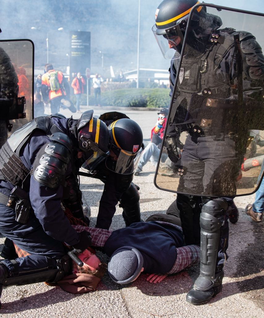 un CRS appuie sur la capuche d'un militant