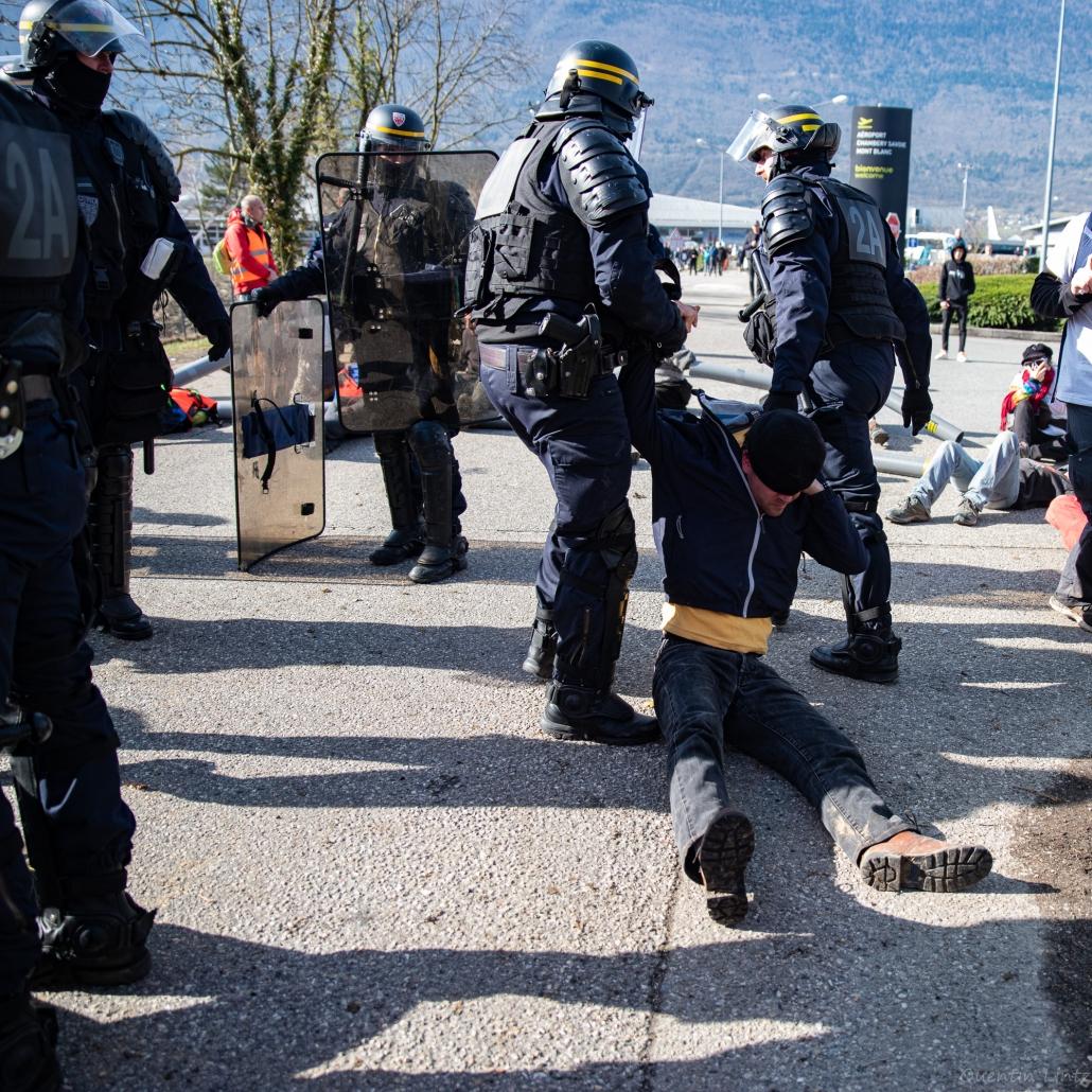 un militant se fait trainer au sol par deux CRS