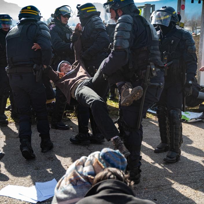 un militant se fait transporter vers l'exterieur