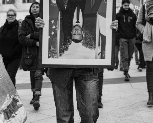 un manifestant tient le protrait de macron en sens inverse