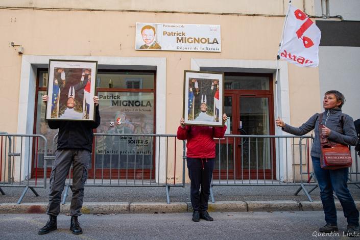 deux manifestant.es tiennent des portraits de macron à l'envers