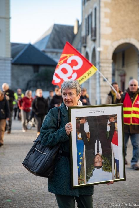 une manifestante tien le portrait de macron à l'envers