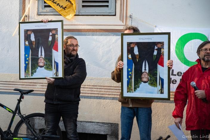 deux militant tiennent les portraits de macron à l'envers à coté de la préfecture de savoie à chambéry