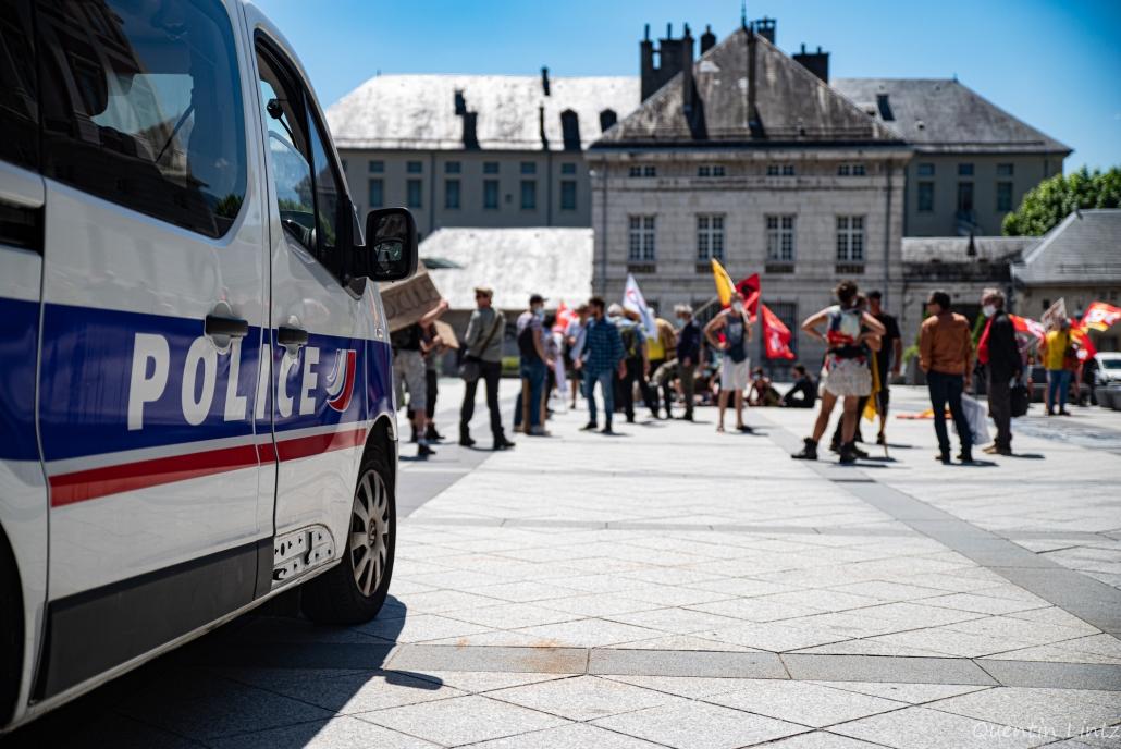 voiture de police devant les manifestant.es