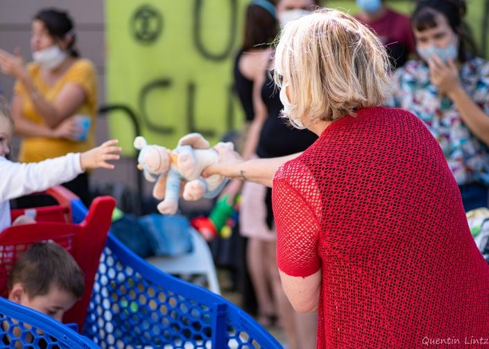 une maman donne une peluche à son enfant